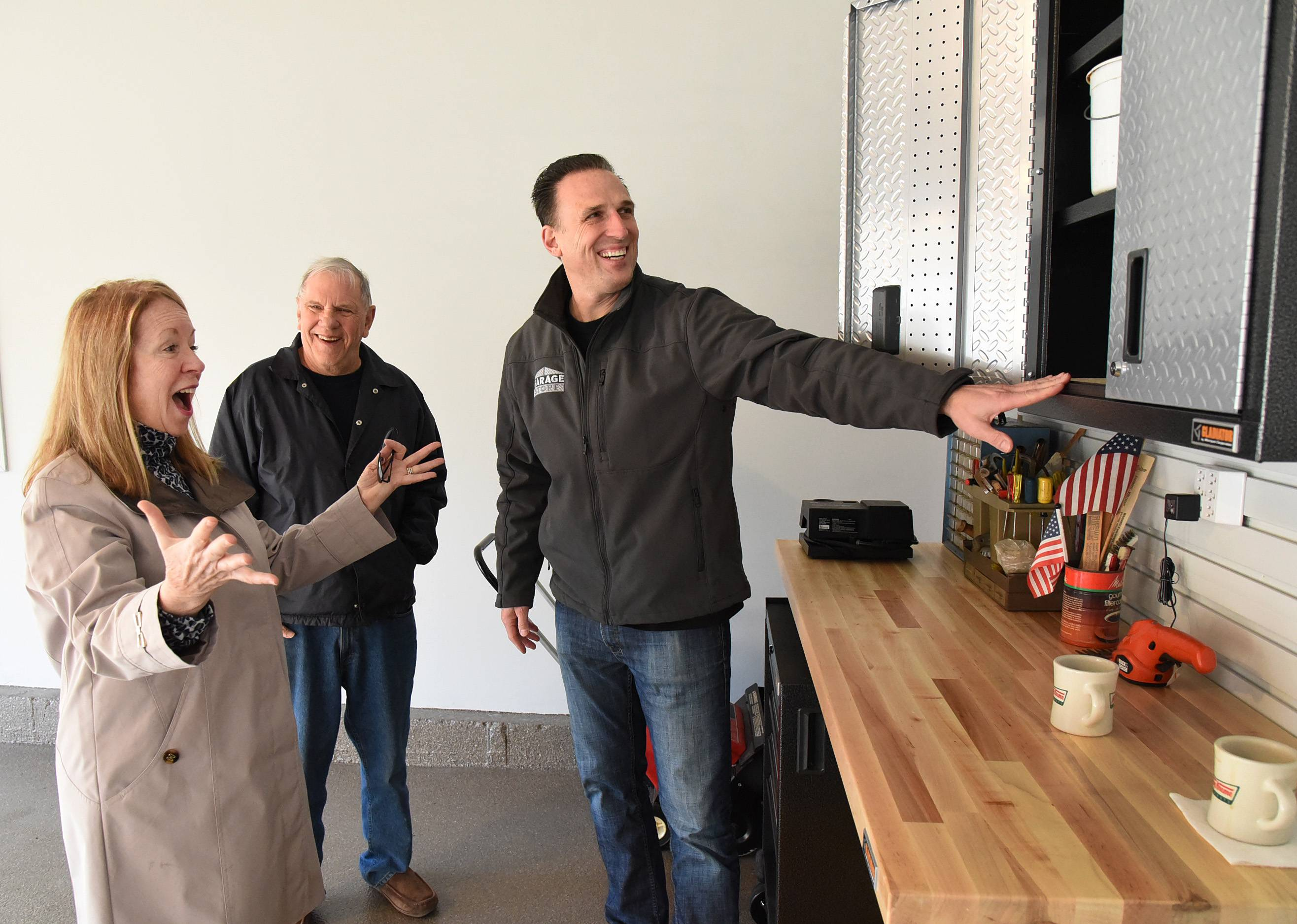 Garage Store owner Jim Melchert shows garage makeover winners Gary and Susan Heitsch of Palatine their new storage cabinets last fall.