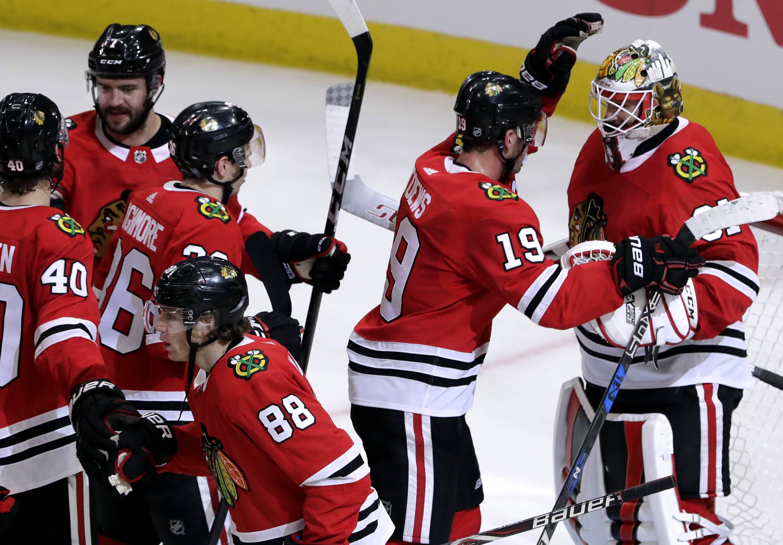 Chicago Blackhawks goalie Anton Forsberg, right, celebrates with center Jonathan Toews after the Blackhawks defeated the Boston Bruins 3-1 in an NHL hockey game Sunday, March 11, 2018, in Chicago.