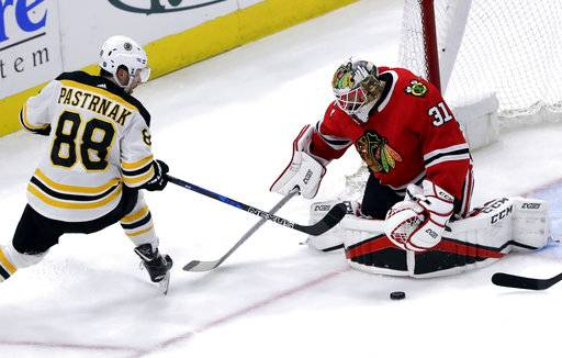 Chicago Blackhawks goalie Anton Forsberg, right, blocks a shot by Boston Bruins right wing David Pastrnak during the second period of an NHL hockey game Sunday, March 11, 2018, in Chicago.