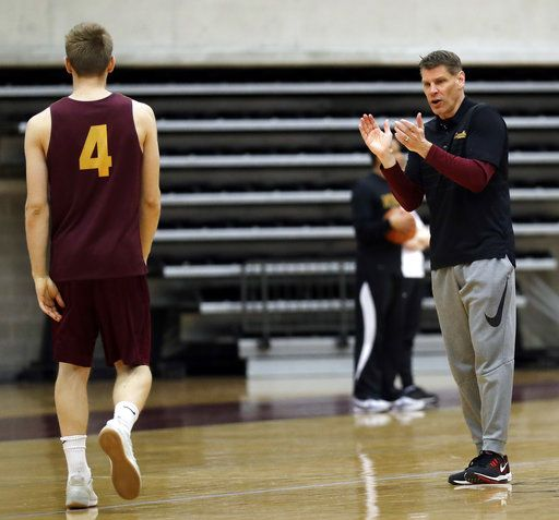 Loyola head coach Porter Moser, right, cheers as he talks to guard Bruno Skokna during NCAA college basketball practice in Chicago, Friday, March 9, 2018. Loyola locks up 1st March Madness appearance in 33 years.