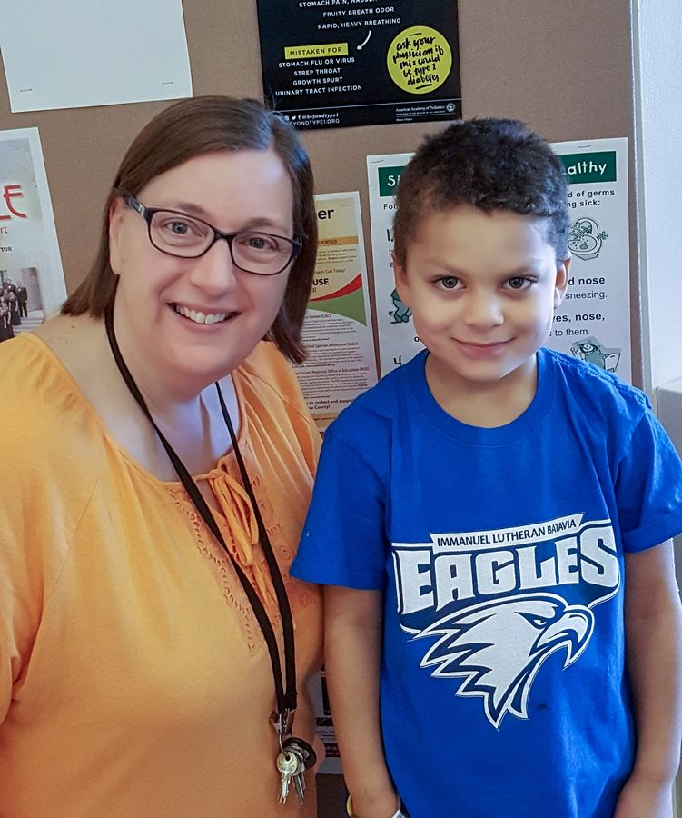 Donna Laughlin, principal of Immanuel Lutheran School in Batavia, poses with Jayce Benedetto in front of the posters about the signs and symptoms of Type 1 diabetes.
