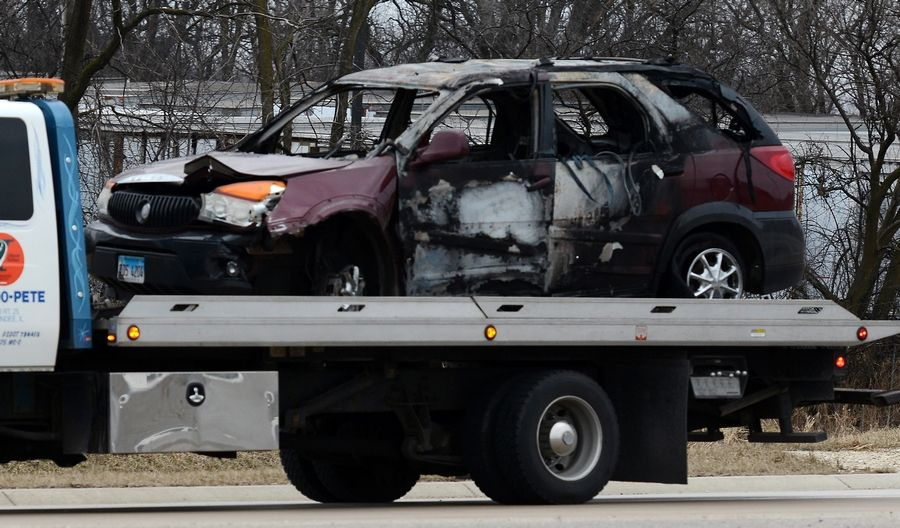 A tow truck takes away a burned vehicle from westbound Interstate 90 near Elgin Monday morning after its 34-year-old female driver died earlier in the day in an officer-involved shooting earlier.