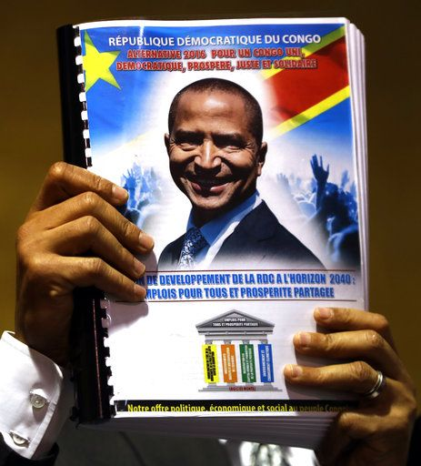 Congolese opposition leader, Moise Katumbi, holds a document with his own face as he addresses a three-day forum of delegates at a resort hotel near Johannesburg, South Africa, Monday, March 12, 2018. Congolese opposition leader and other figures opposed to longtime President Joseph Kabila met in South Africa on Monday to build a coalition ahead of long-delayed elections in the turbulent, resource-rich country.
