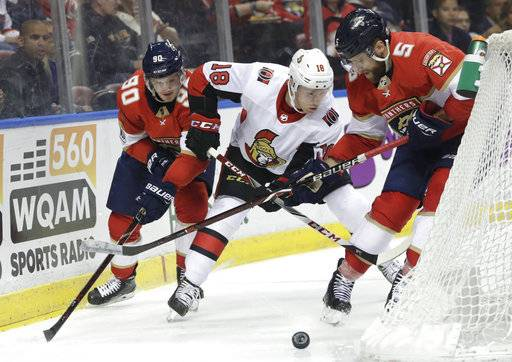 Florida Panthers' Jared McCann (90) and Aaron Ekblad (5) go for the puck against Ottawa Senators' Ryan Dzingel (18) during the second period of an NHL hockey game, Monday, March 12, 2018, in Sunrise, Fla.