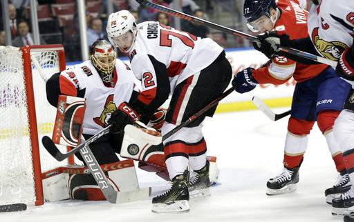 Florida Panthers' Frank Vatrano, right, attempts a shot on goal as Ottawa Senators goaltender Craig Anderson makes a save as Senators' Thomas Chabot (72) looks on during the first period of an NHL hockey game, Monday, March 12, 2018, in Sunrise, Fla.