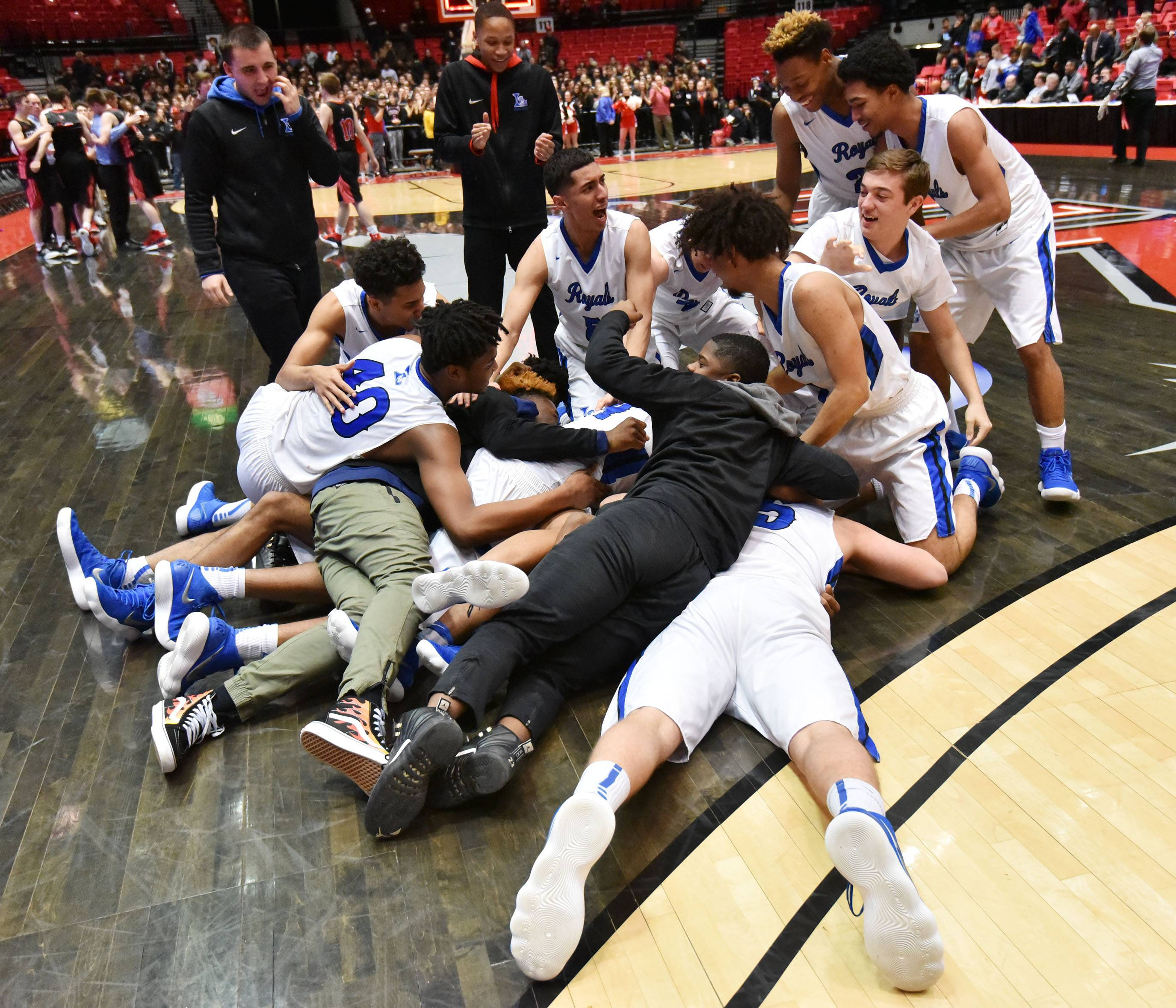 Larkin players pile together after beating Benet in the Class 4A supersectional boys basketball game at Northern Illinois University Tuesday.