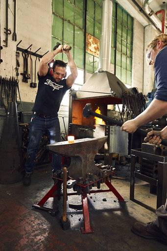This April 2017 provided by Robert Thomas shows Thomas, left, working with Matt Garton to make a custom blacksmith tool at the RTID studio in North Charleston, S.C. (Sully Sullivan/Robert Thomas via AP)