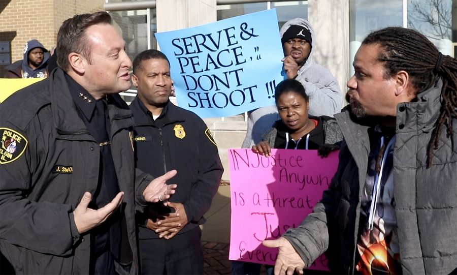 Elgin Police Chief Jeff Swoboda, left, exchanges words with Marcus Banner of Elgin as a rally was held in front of the Elgin Police Department Tuesday in the wake of Monday's police-involved shooting death of Decynthia Clements.