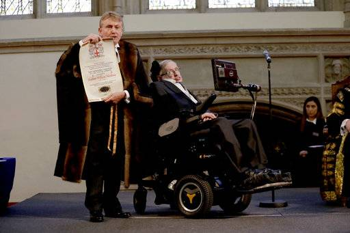 FILE - In this March 6, 2017 file photo, Britain's Professor Stephen Hawking is presented with his illuminated Freedom scroll by the Chamberlain of the City of London Peter Kane as he receives the Honorary Freedom of the City of London during a ceremony at the Guildhall in the City of London. Hawking, whose brilliant mind ranged across time and space though his body was paralyzed by disease, has died, a family spokesman said early Wednesday, March 14, 2018.