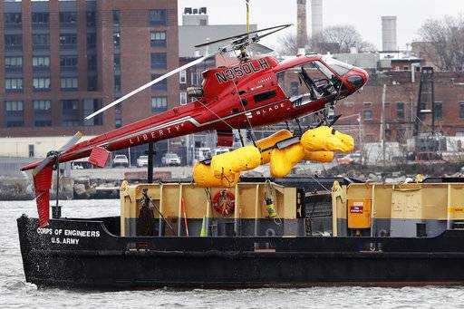 A helicopter is hoisted by crane from the East River onto a barge, Monday, March 12, 2018, in New York. The pilot was able to escape the Sunday night crash after the aircraft flipped upside down in the water killing several passengers, officials said. (AP Photo/Mark Lennihan)