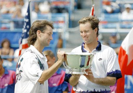FILE - In this Sept. 10, 1993, file photo, Ken Flach, left, of Alpharetta, Ga., and Rick Leach, right, of Laguna Beach, Calif., check out the winner's trophy after taking the U.S. Open men's doubles title in New York. Flach, who won four Grand Slam titles in men's doubles and two in mixed doubles, died Monday night, March 12, 2018, in California after a brief illness, the ATP World Tour and International Tennis Federation announced Tuesday, March 13, 2018. He was 54.