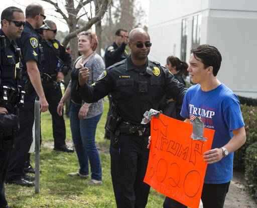 Officers separate a supporter of President Donald Trump and a protester Tuesday, March 13, 2018, in San Diego. Trump's visit was greeted with peaceful protests by demonstrators both for and against his planned wall.