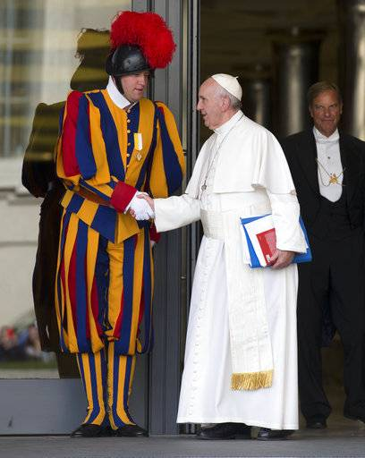 FILE - In this Oct. 16, 2015 file photo, Pope Francis shakes hands with a Vatican Swiss guard as he leaves after a morning session of the Synod of bishops, at the Vatican. When Cardinal Mario Jorge Bergoglio appeared five years ago, on March 13, 2013, at the main window of St. Peter's Loggia in a white cassock and without solemnity greeted the chanting crowd in the square with a casual 'buonasera' (good evening) it was immediately apparent that Pope Francis's style would be different, folksier than that of other popes. (AP Photo/Alessandra Tarantino, file)