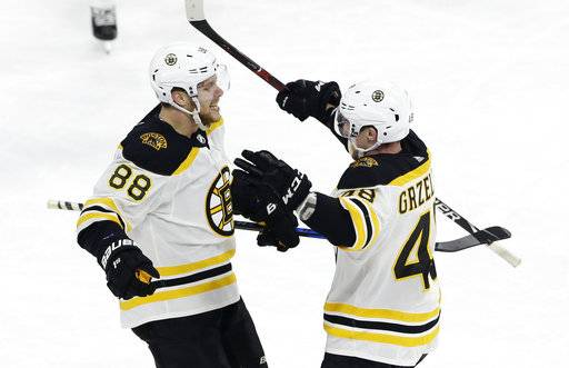 Boston Bruins' David Pastrnak (88), of the Czech Republic, is congratulated by Matt Grzelcyk (48) following Pastrnak's game winning goal against the Carolina Hurricanes during the third period of an NHL hockey game in Raleigh, N.C., Tuesday, March 13, 2018. Boston won 6-4. (AP Photo/Gerry Broome)
