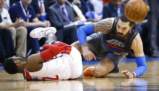 FILE - In this Jan. 25, 2018, file photo, Washington Wizards guard John Wall (2) and Oklahoma City Thunder center Steven Adams, right, tumble to the court during the fourth quarter of an NBA basketball game in Oklahoma City. Wizards coach Scott Brooks is not entirely sure when All-Star point guard John Wall will return to full-fledged practicing after missing 1 and a half months so far because of surgery on his left knee. Wall last played on Jan. 25, and his operation was Jan. 31. (AP Photo/Sue Ogrocki, File)