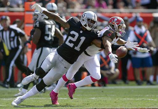 FILE - In this Oct. 30, 2016, file photo, Oakland Raiders cornerback Sean Smith (21) breaks up a pass intended for Tampa Bay Buccaneers wide receiver Cecil Shorts (10) during the first quarter of an NFL football game, in Tampa, Fla. The Raiders are releasing cornerback Sean Smith to create more salary cap room heading into free agency. A person familiar with the move said Smith was told Monday, March 12, 2018, that he will be let go before the start of the new league year on Wednesday. The person spoke on condition of anonymity because the team hadn't announced the move. (AP Photo/Jason Behnken, File)