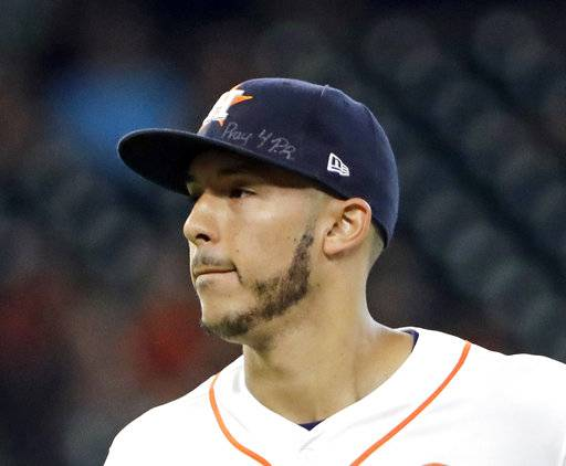 FILE - This is a Sept. 23, 2017, file photo showing Houston Astros shortstop Carlos Correa wears a message on his cap for those affected by the Hurricane in Puerto Rico during the second inning of a baseball game. Correa skipped the Astros' visit to the White House, Monday, March 12, 2018, to help arrange for more relief supplies for shipment to hurricane-ravaged Puerto Rico, where he grew up. (AP Photo/David J. Phillip, File)