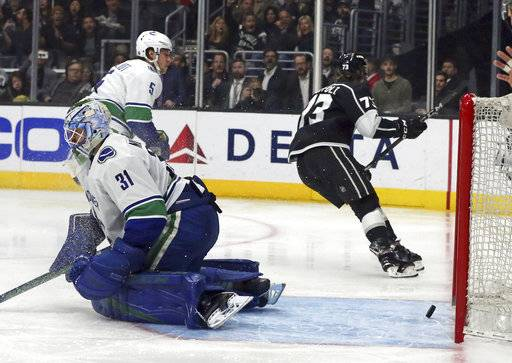 Los Angeles Kings right winger Dustin Brown (23) puts the puck past Vancouver Canucks goalie Anders Nilsson (31) for a goal in the second period of an NHL hockey game in Los Angeles, Monday, March 12, 2018.