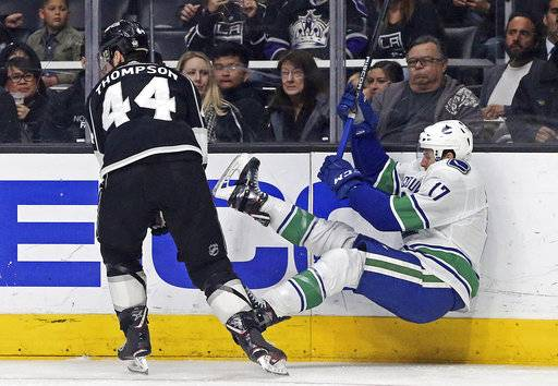 Los Angeles Kings center Nate Thompson (44) and Vancouver Canucks center Nic Dowd (17 tangle in the first period of an NHL hockey game in Los Angeles, Monday, March 12, 2018.