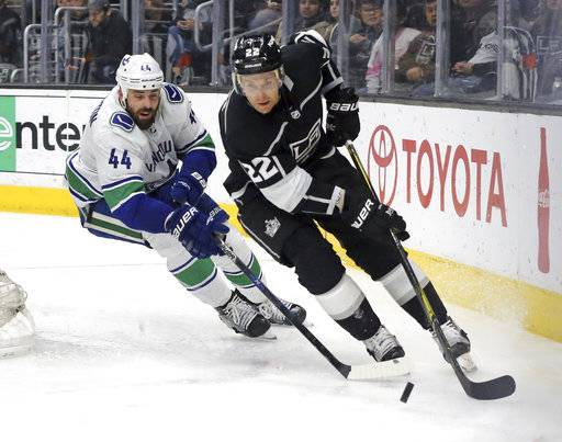 Los Angeles Kings center Trevor Lewis (22) and Vancouver Canucks defenseman Erik Gudbranson (44) chase the puck in the second period of an NHL hockey game in Los Angeles, Monday, March 12, 2018.