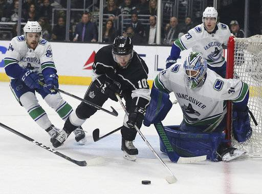 Vancouver Canucks goalie Anders Nilsson (31) and Los Angeles Kings center Tobias Rieder (11) and others battle at the goal in the second period of an NHL hockey game in Los Angeles, Monday, March 12, 2018.