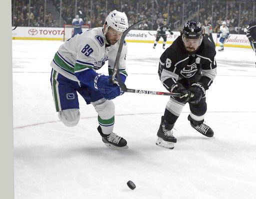 Vancouver Canucks center Sam Gagner (89) and Los Angeles Kings defenseman Drew Doughty (8) chase the puck in the first period of an NHL hockey game in Los Angeles, Monday, March 12, 2018.