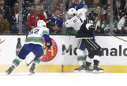 Vancouver Canucks center Bo Horvat (53) and defenseman Michael Del Zotto (4) collide with Los Angeles Kings center Alex Iafallo (19) in the first period of an NHL hockey game in Los Angeles, Monday, March 12, 2018.