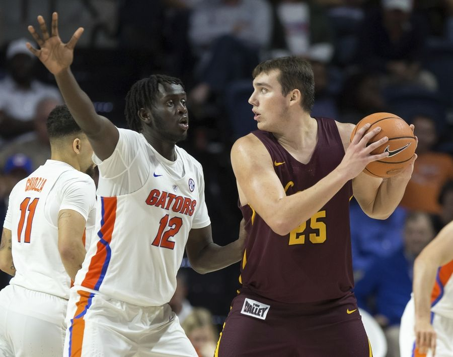 Loyola of Chicago center Cameron Krutwig (25) looks to pass around Florida center Gorjok Gak (12) during the second half of an NCAA college basketball game in Gainesville, Fla., Wednesday, Dec. 6, 2017. Loyola of Chicago won 65-59.
