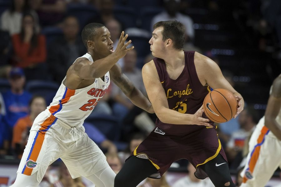 Loyola of Chicago center Cameron Krutwig (25) looks to pass around Florida forward Keith Stone (25) during the second half of an NCAA college basketball game in Gainesville, Fla., Wednesday, Dec. 6, 2017. Loyola of Chicago won 65-59.
