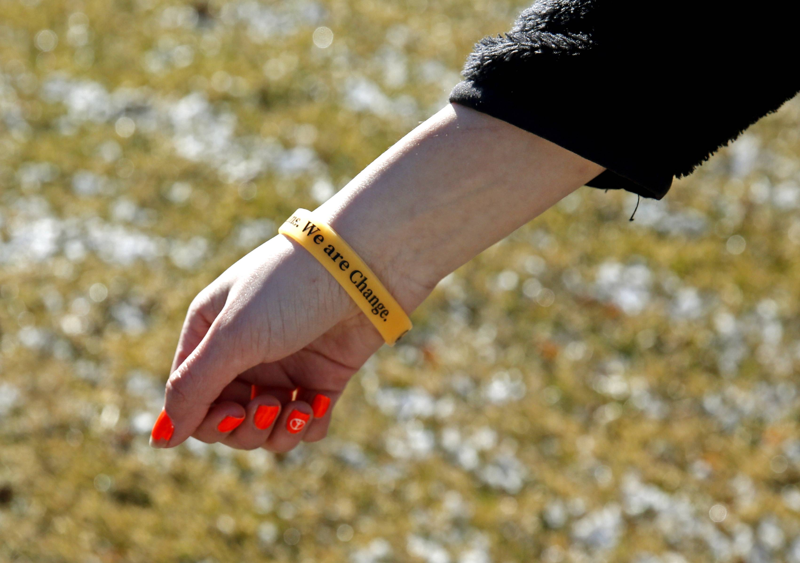 A Neuqua Valley High School senior shows her solidarity bracelet during the Wednesday walkout by students in the suburbs and around the country to draw attention to the issue of gun violence.