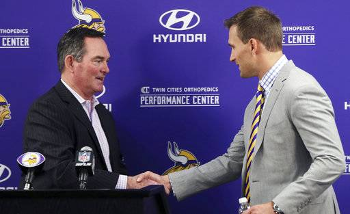 Minnesota Vikings new quarterback Kirk Cousins, right, is welcomed to the podium by head coach Mike Zimmer before addressing the media at a news conference after he was introduced after signing a three-year, $84 million contract at the NFL football team's new headquarters Thursday, March 15, 2018, in Eagan, Minn.