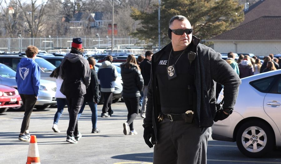Officer Dusan Racic watches students during the Libertyville High School walkout Wednesday.