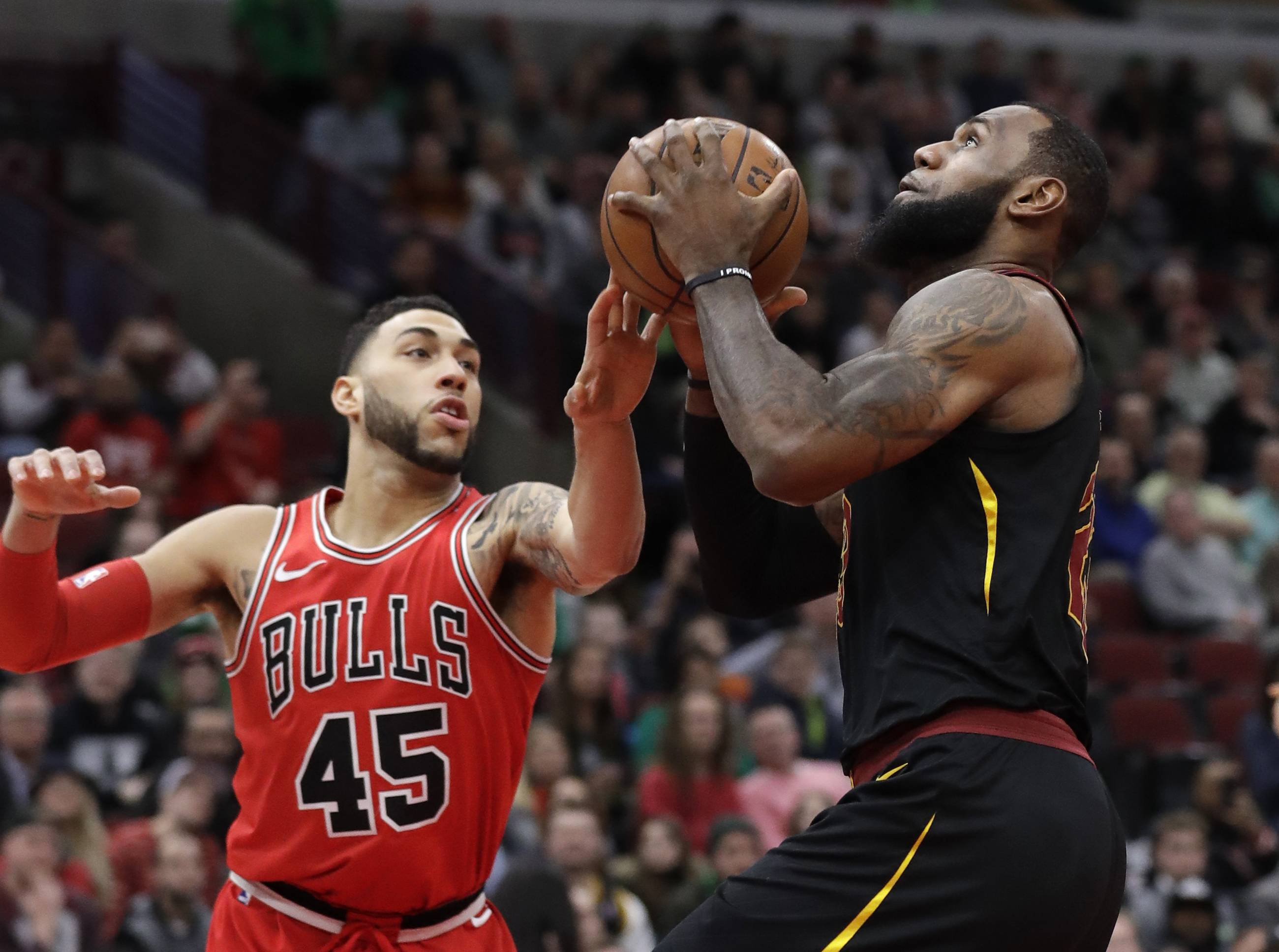 Cleveland Cavaliers forward LeBron James, right, drives to the basket against Chicago Bulls guard Denzel Valentine during the first half of an NBA basketball game Saturday, March 17, 2018, in Chicago. (AP Photo/Nam Y. Huh)