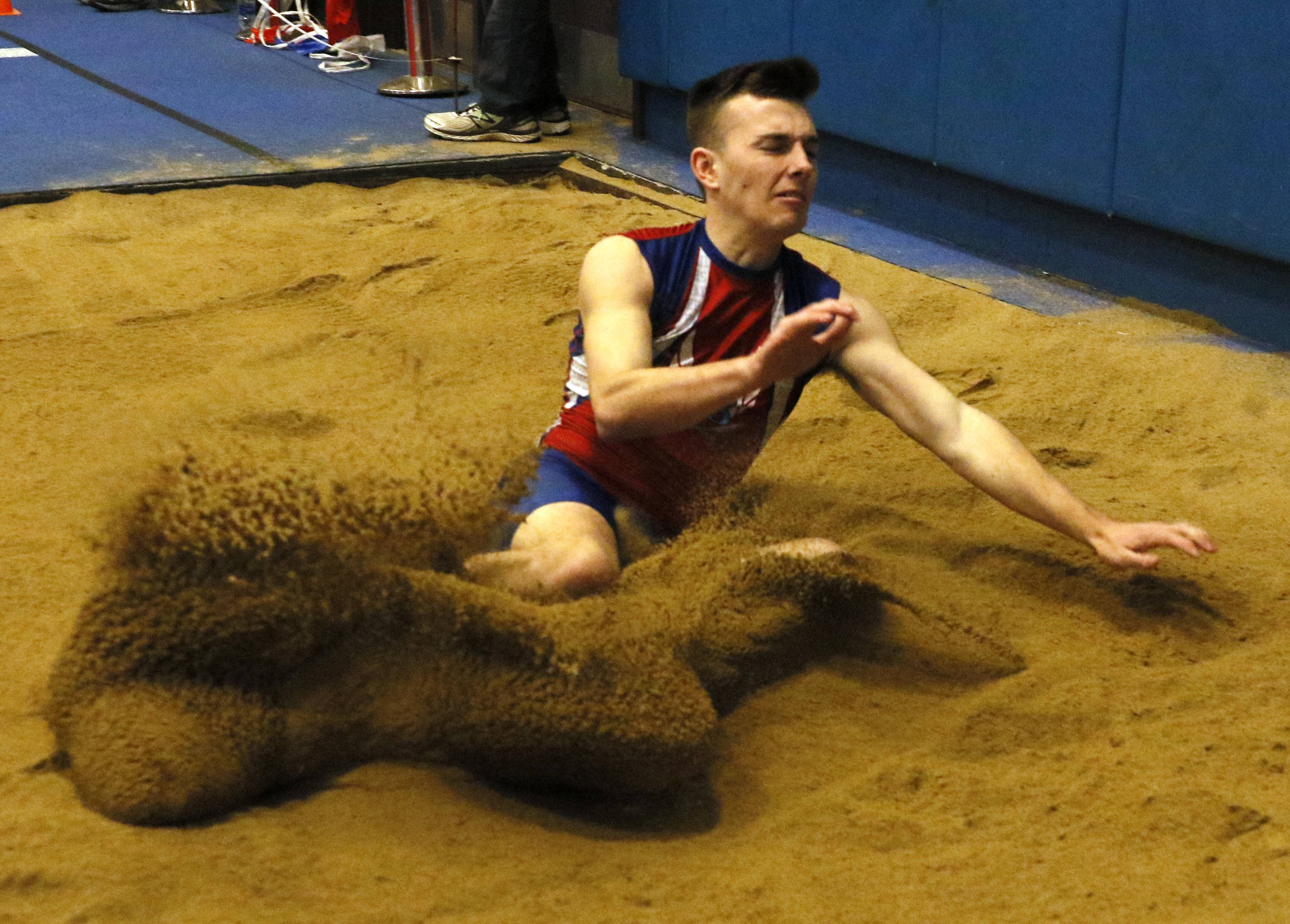 Glenbard South's Michael Zima completes his long jump during the Metro Suburban Conference boys indoor track meet at Glenbard South High School.