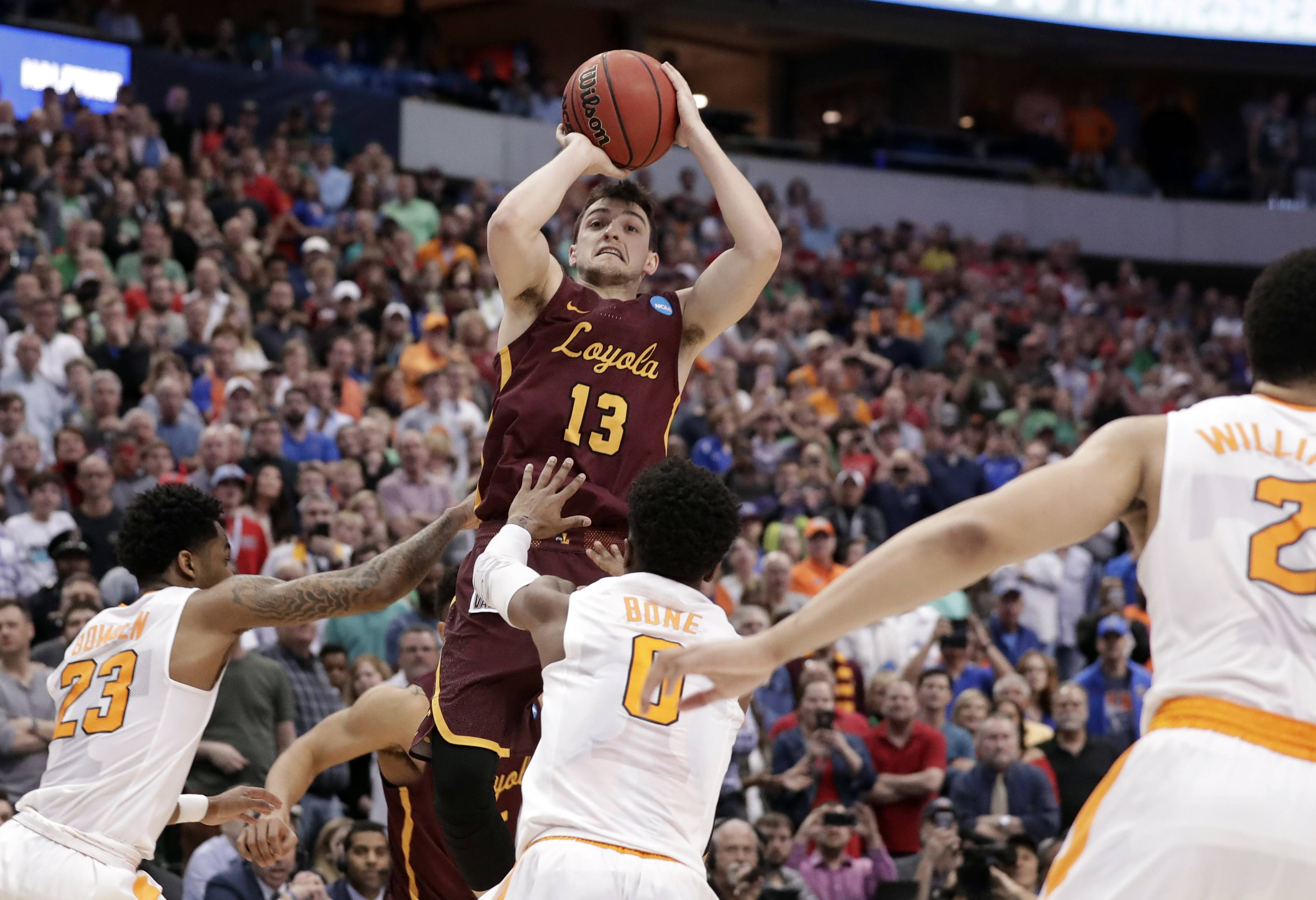 Loyola-Chicago guard Clayton Custer (13) shoots over Tennessee's Jordan Bowden (23) and Jordan Bone (0) to score in the final seconds of a second-round game at the NCAA men's college basketball tournament in Dallas, Saturday. The shot helped Loyola to a 63-62 win.