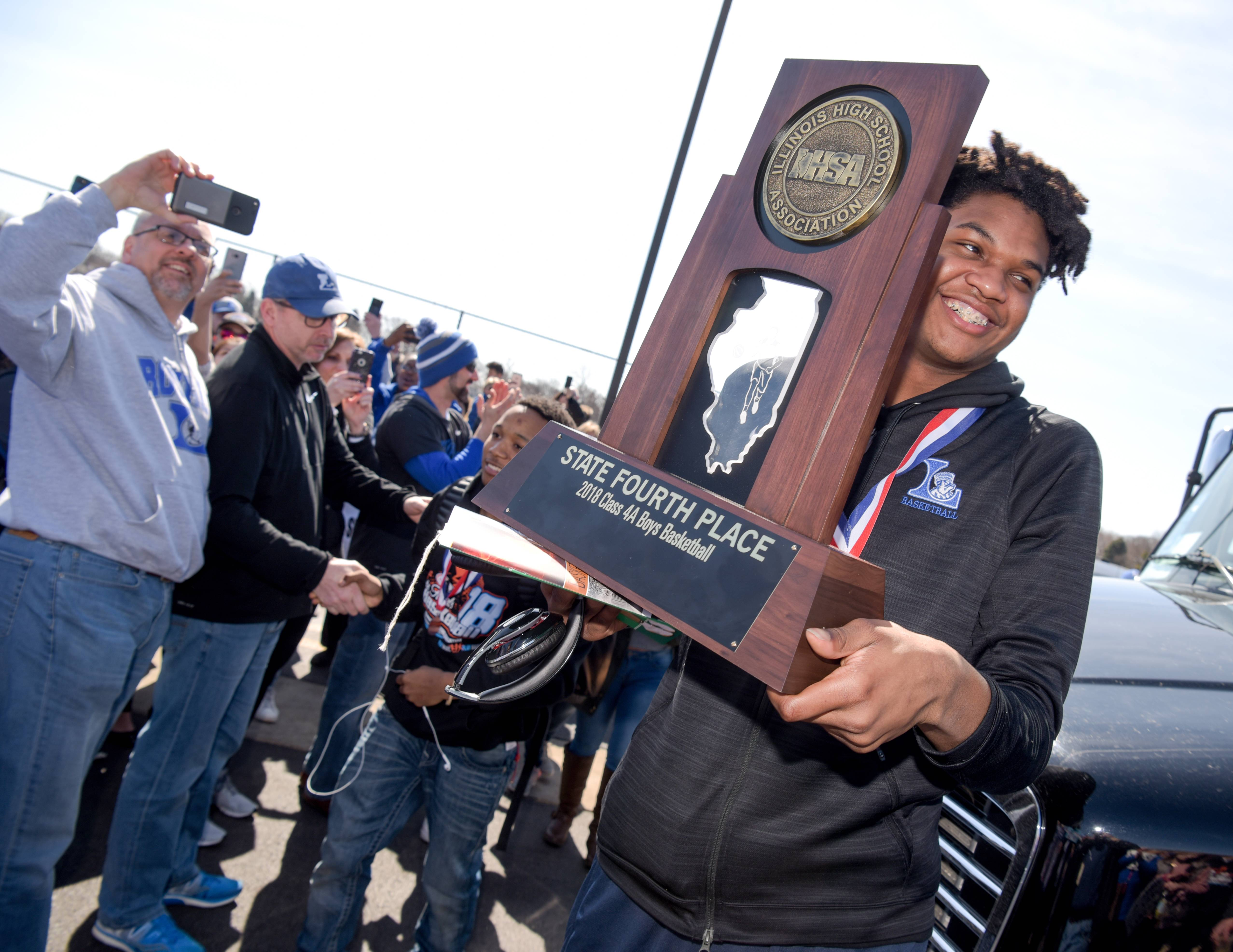 Larkin High School boys basketball player Jalen Shaw holds up the 4th place 4A Boys Basketball trophy Sunday as the team returns home to cheering fans.