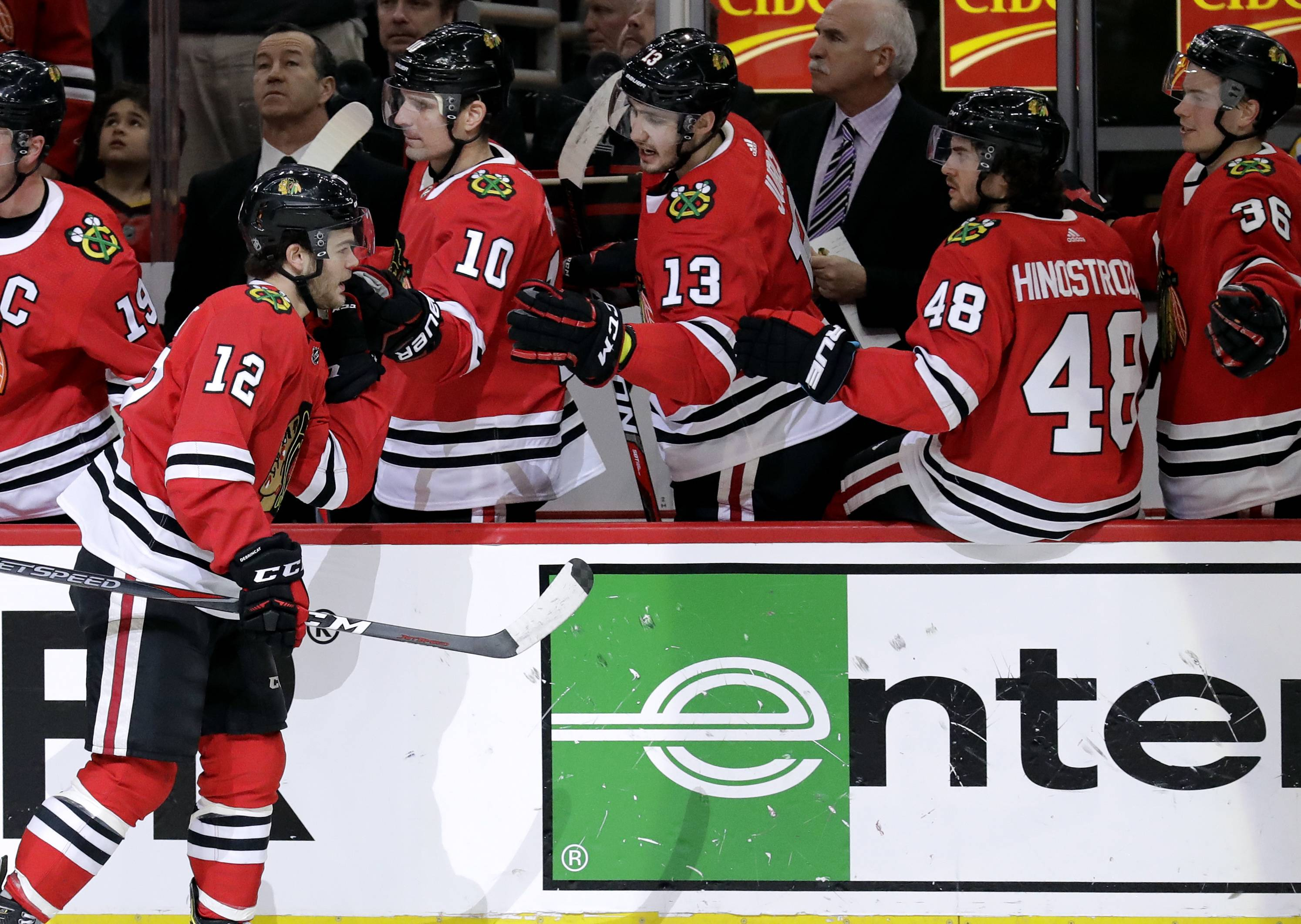 Chicago Blackhawks right wing Alex DeBrincat (12) celebrates with teammates after scoring a goal during the first period of an NHL hockey game against the St. Louis Blues, Sunday, March 18, 2018, in Chicago. (AP Photo/Nam Y. Huh)