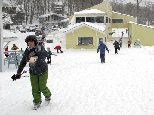 In this March 15, 2018, photo, skiers head to the slopes at Mad River Glen in Fayston, Vt. Three successive March snowstorms have provided good conditions for late-season skiing.
