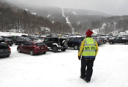 In this March 15, 2018, photo, an employee of the Mad River Glen ski area, in Fayston, Vt., directs skiers where to park in a lot filled with vehicles. Three successive March snowstorms have provided good conditions for late-season skiing.