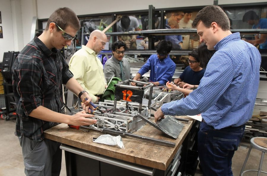 Wheeling High School junior Daniel Sobas, left, works on a robot as Luke Mehringer of Engus Corp. asks him questions during the school's Manufacturing Open House on Monday. The school provided tours of its manufacturing and engineering labs.