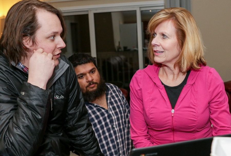 Carole Cheney looks at some early results for the 6th Congressional District race Tuesday with campaign manager Caleb Thompson, left, and field coordinator Rajah Sandor, center, at her home in Naperville.