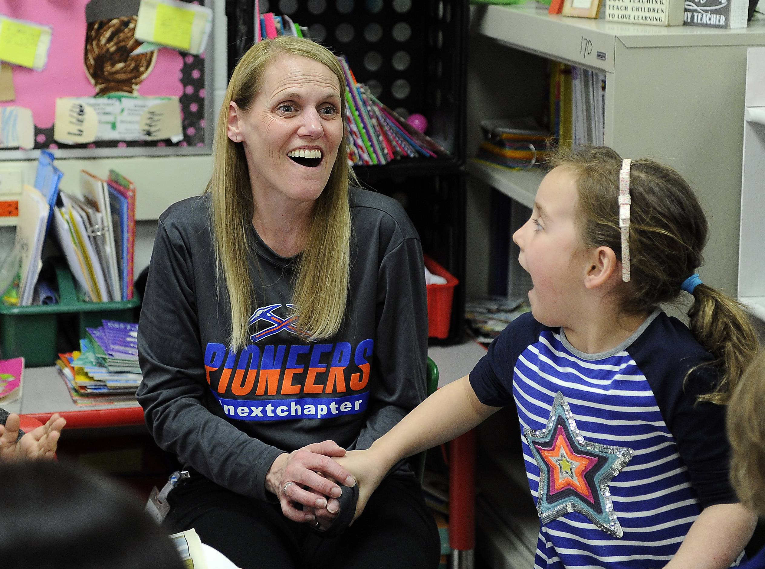 "A stunned Lisa Buchholz learns she received the Golden Apple Award for Excellence in Teaching during a surprise announcement Wednesday at Abraham Lincoln Elementary in Glen Ellyn. ""I'm speechless here,"" said Buchholz, alongside student Teagan Burke."