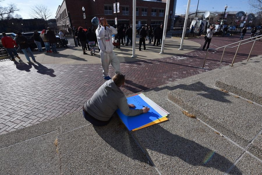A woman makes signs for protesters after a news conference to release the video of a fatal police shooting Thursday at the Elgin Police Department.