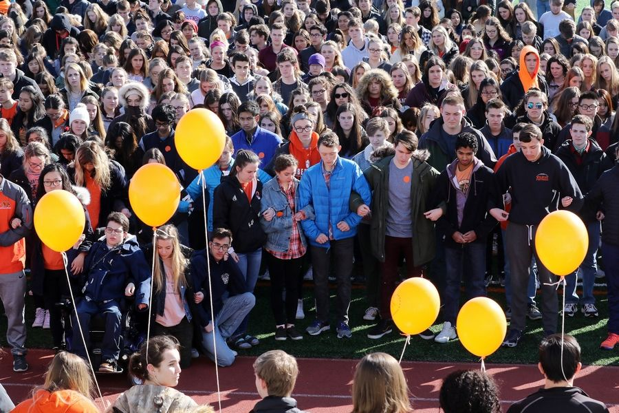 Students stood in silence after walking out of Libertyville High School March 14, as part of a nationwide protest against gun violence. More protests are planned across the globe Saturday.