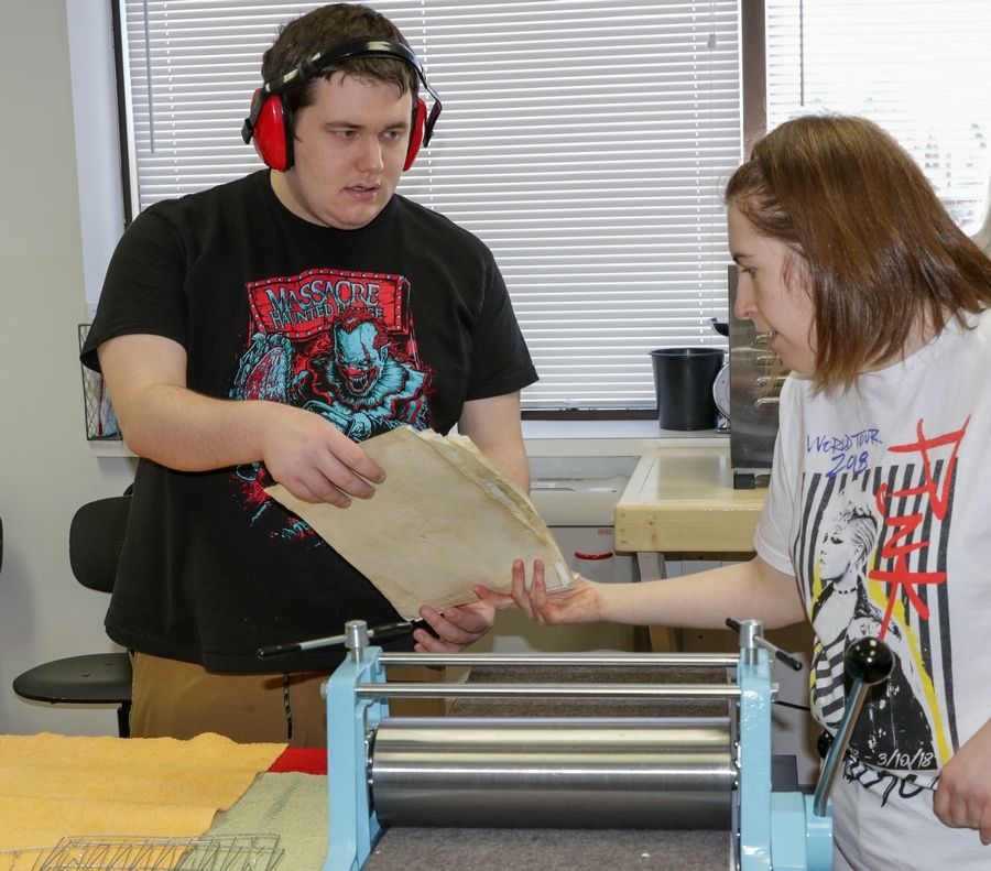 Student Ben Clark hands paper to volunteer Libby DeTamble as they make paper for wedding invitations at the microConnections business in the Connections program for Naperville Unit District 203 young adult students with disabilities.