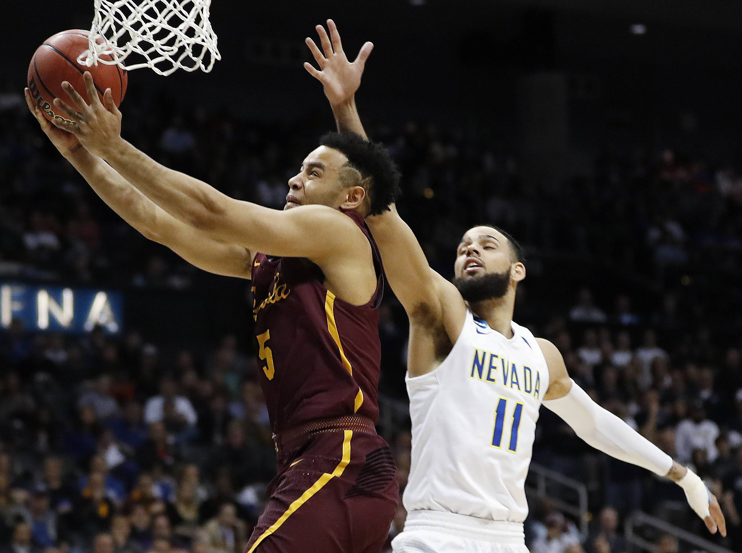 Loyola guard Marques Townes (5) moves to the hoop as Nevada forward Cody Martin (11) defends during the second half Thursday, in Atlanta.