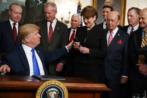 President Donald Trump hands a pen to Lockheed Martin CEO Marillyn Hewson after signing a presidential memorandum imposing tariffs and investment restrictions on China, in the Diplomatic Reception Room of the White House, Thursday, March 22, 2018, in Washington.