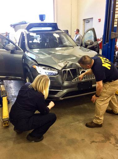 In this March 20, 2018, photo provided by the National Transportation Safety Board, investigators examine a driverless Uber SUV that fatally struck a woman in Tempe, Ariz. The fatality prompted Uber to suspend all road-testing of such autos in the Phoenix area, Pittsburgh, San Francisco and Toronto. (National Transportation Safety Board via AP)