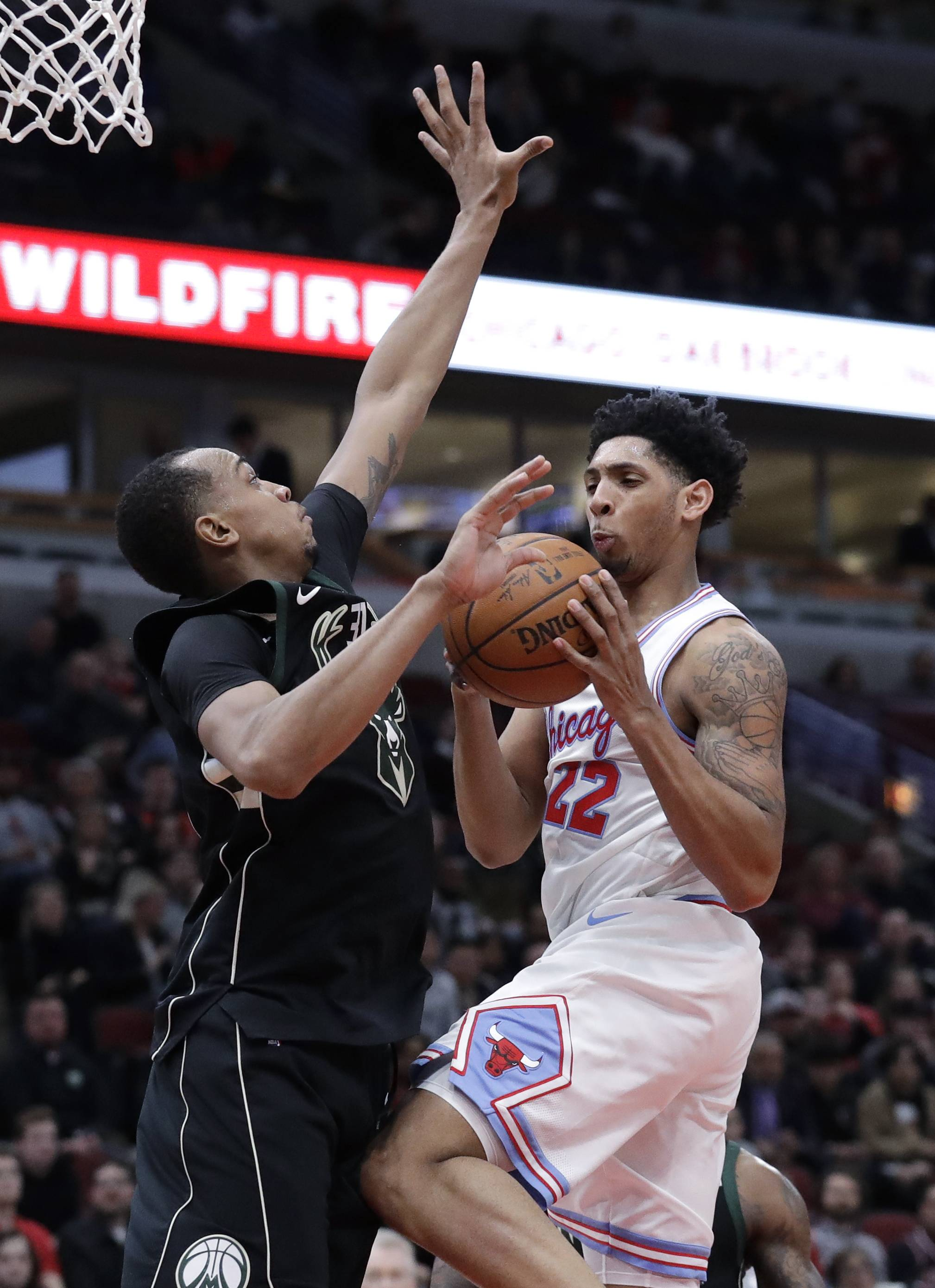 Milwaukee Bucks forward John Henson, left, guards Chicago Bulls guard Cameron Payne during the second half of an NBA basketball game Friday, March 23, 2018, in Chicago. (AP Photo/Nam Y. Huh)
