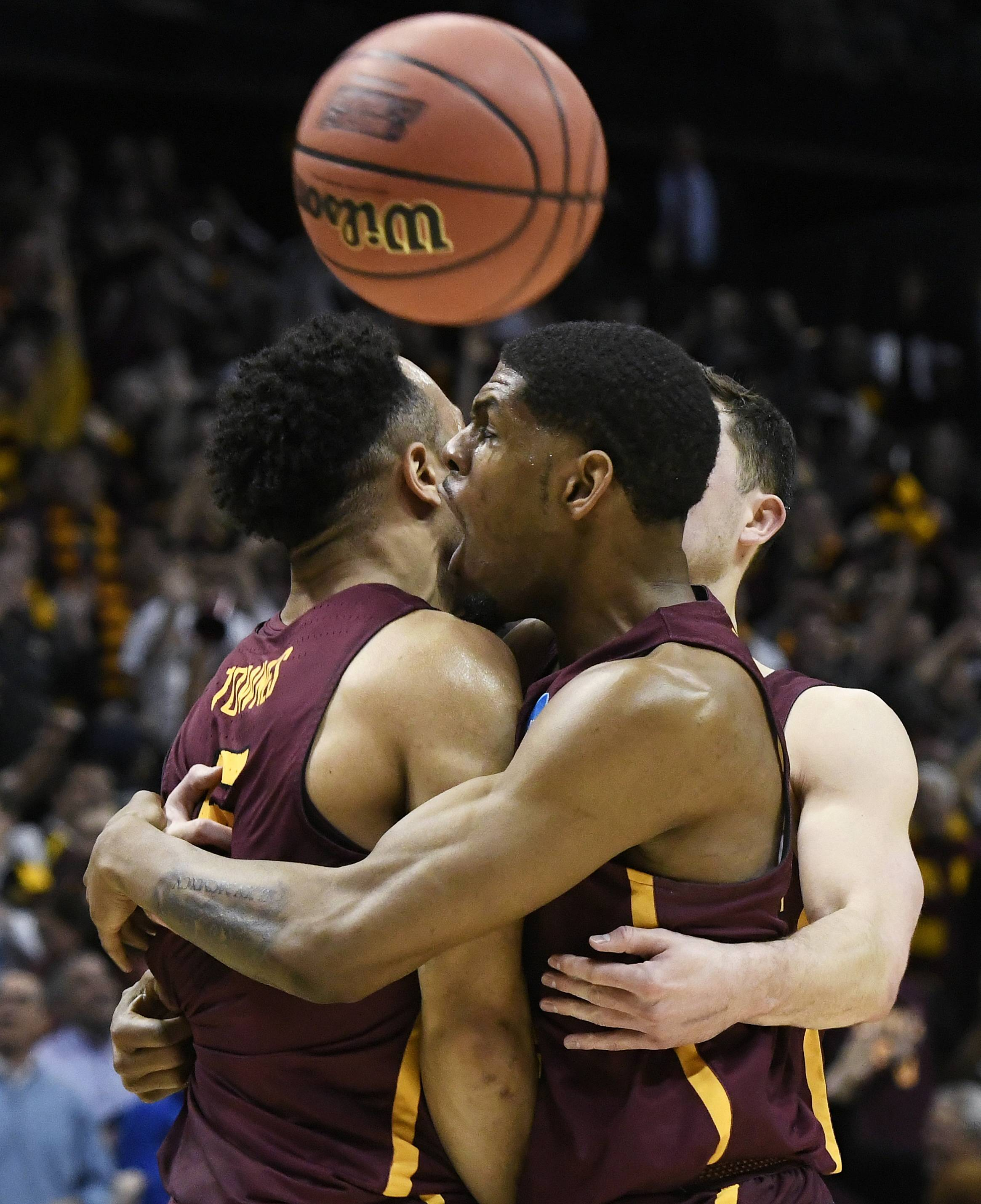 Loyola guard Marques Townes, left, his embraced my teammates after his three-point shot against Nevada during the second half of a regional semifinal NCAA college basketball game, Thursday in Atlanta. Loyola has captured the city's imagination in the past couple of weeks with its surprising run to the Elite Eight. Before the Ramblers face Kansas State in the regional final on Saturday, get caught up on what makes this team so great.